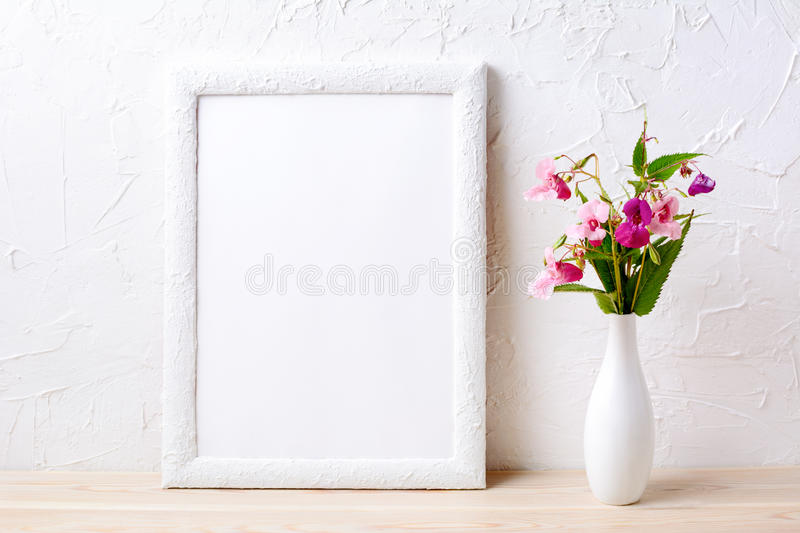 White frame mockup with pink flowers in elegant vase royalty free stock photography