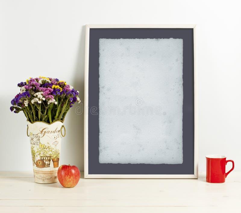 White frame mockup with plant pot, mug and apple on wooden shelf. Empty frame mock up for presentation design. Template framing for modern art royalty free stock images
