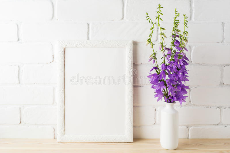 White frame mockup with purple campanula bouquet near brick wall. Empty frame mock up for presentation design. Template framing for modern art royalty free stock photography
