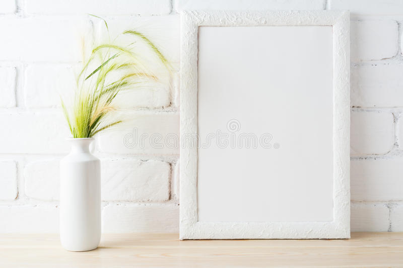 White frame mockup with wild grass ears near painted brick wall. White frame mockup with golden yellow and green wild grass ears in styled vase near painted stock photo