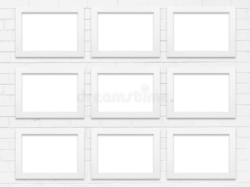 White Frames. Equally spaced white wooden picture frames on a white brick wall with space for copy or image stock photo