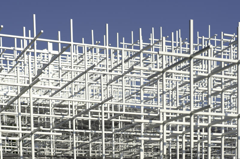 White framework. A metal framework of squares seen from below against a blue sky stock photos