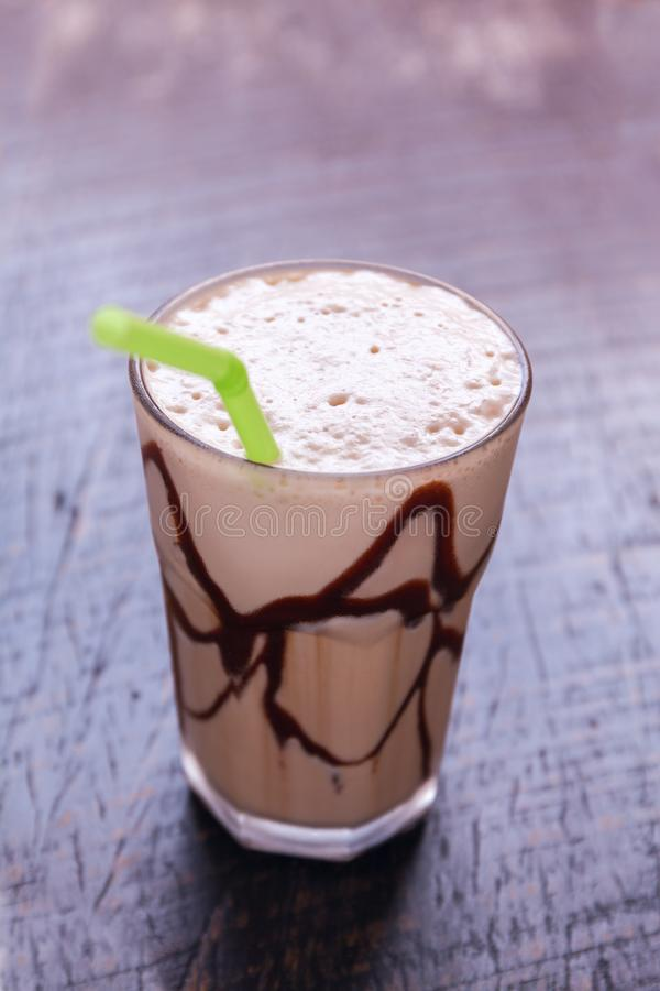 White Frappe Coffee Glass with iced drink on a dark wooden table in a cafe. White Frappe Coffee Glass with iced drink on a dark wooden table in a cafer. Stock royalty free stock photography