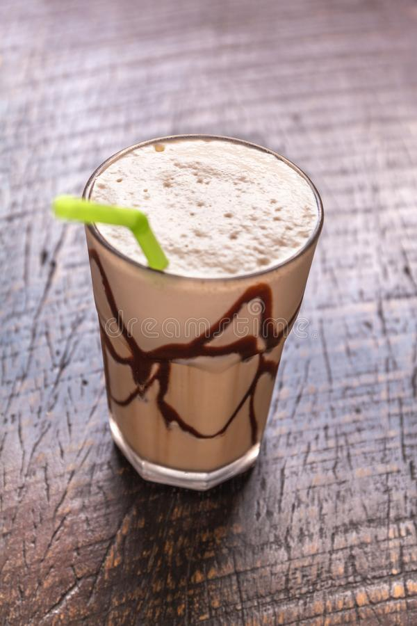 White Frappe Coffee Glass with iced drink on a dark wooden table in a cafe. color correction filter. White Frappe Coffee Glass with iced drink on a dark wooden royalty free stock photos