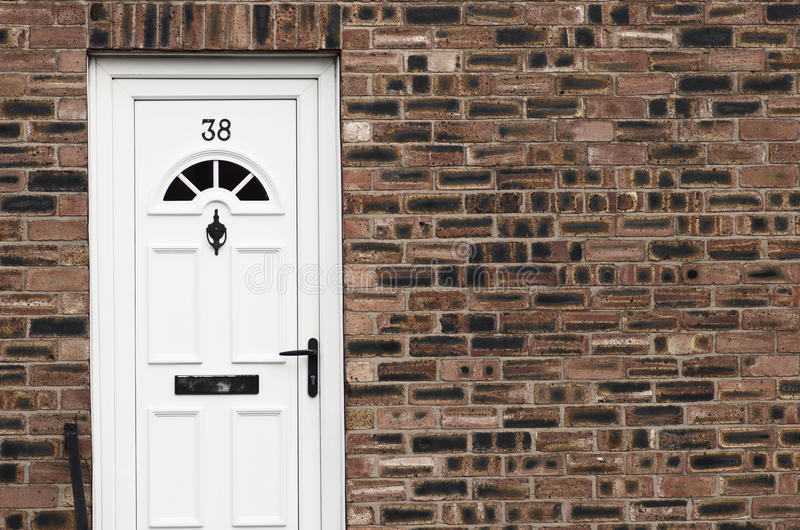 White front door of a red brick English town house. Manchester. stock image