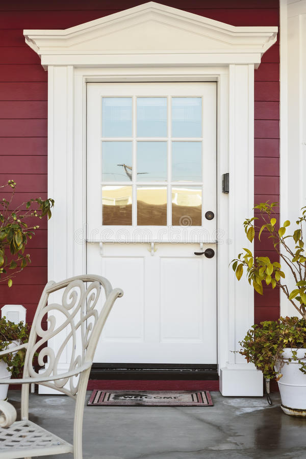 White front door of an upscale home. A white front door of an upscale home. Also seen is red siding, plants, and a patio chair royalty free stock images