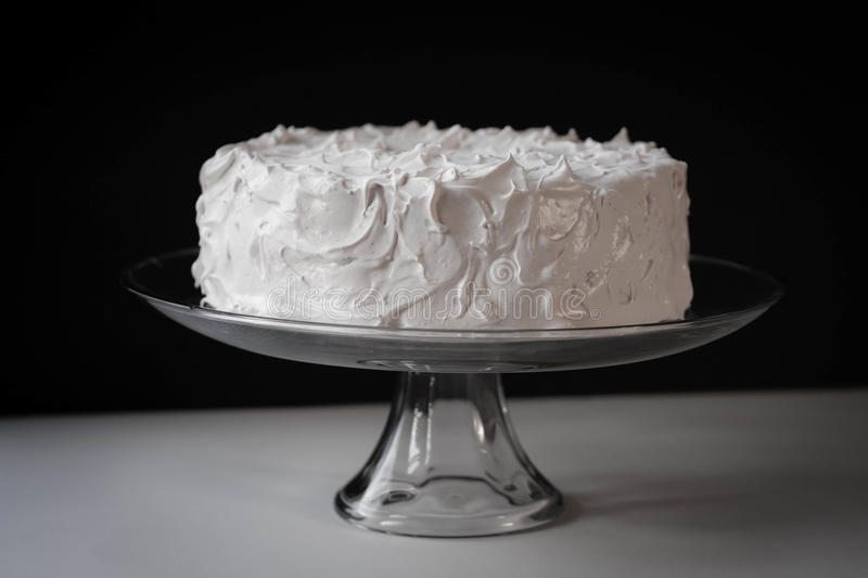 White Frosted Cake on Clear Glass Pedestal. Pure White Frosted Layer Cake on Clear Glass Pedestal with black background stock image