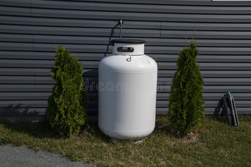 A white fuel tank next to a house. With grey siding between two cedar bushes, bottle, can, cedars, container, equipment, grass, isolated, liquid, metal, nature stock photography