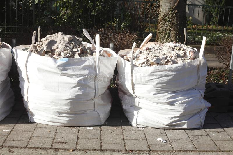 White garbage bags with rubble stones royalty free stock images