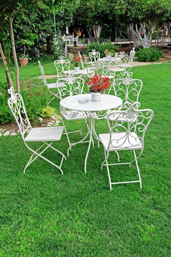 White garden furniture in beautiful garden. stock image