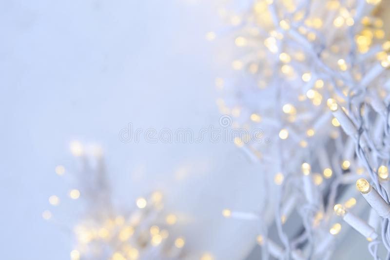 A white garland with flickering yellow lights weighs outside on a background of snow royalty free stock photos