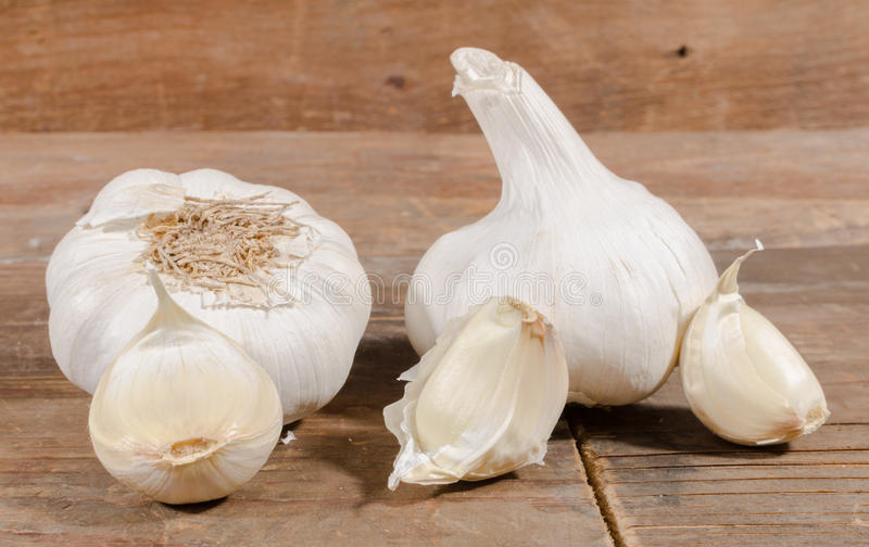 White garlic bulbs and cloves. On wooden background stock photo