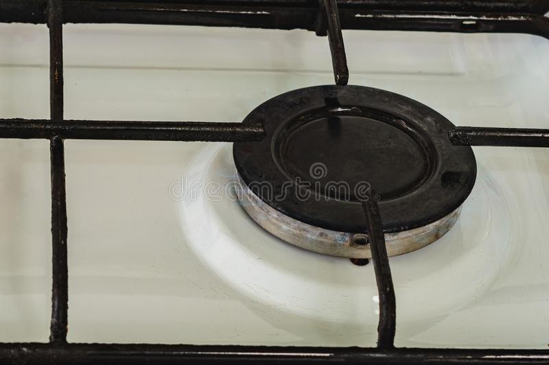 On the white gas stove the burner is lit from which the flame of natural gas is visible. 2019 royalty free stock photography