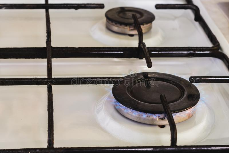 On the white gas stove the burner is lit from which the flame of natural gas is visible. 2019 stock photos