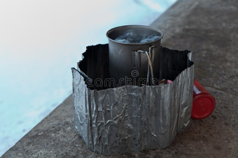 Boiling water in titanium cup on white gas stove royalty free stock photography