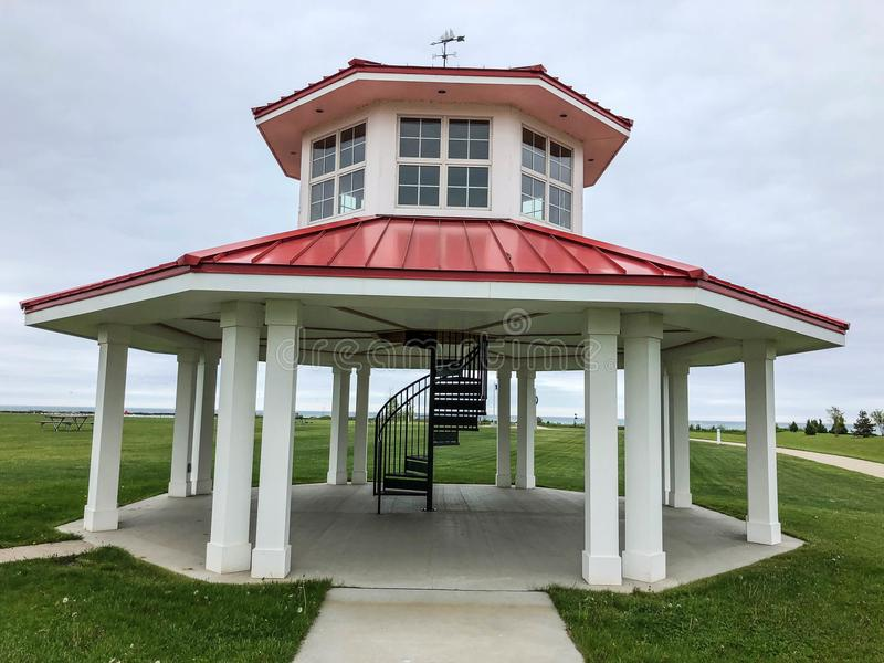 White gazebo with red roof and spiral staircase stock image