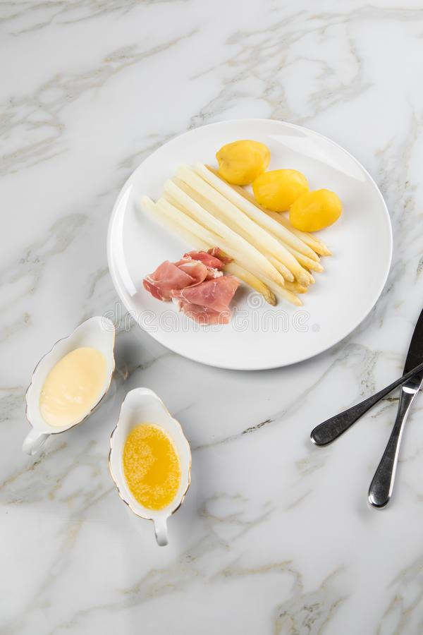 White German asparagus with potatoes, smoked ham, sauce boat with Hollandaise and melted butter on plate and marble background. White German speciality asparagus stock photo