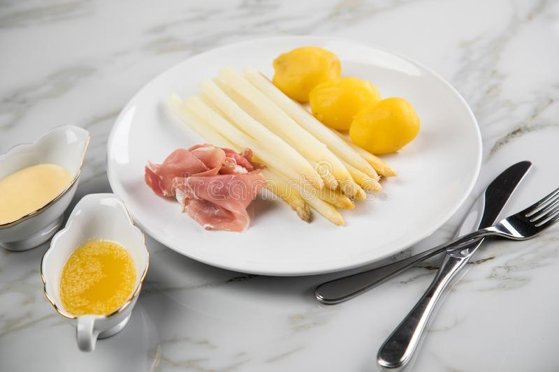 White German asparagus with potatoes, smoked ham, sauce boat with Hollandaise and melted butter on plate and marble background. White German speciality asparagus stock photography