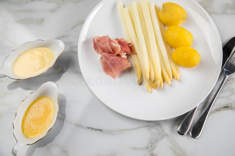 White German asparagus with potatoes, smoked ham, sauce boat with Hollandaise and melted butter on plate and marble background. White German speciality asparagus royalty free stock image