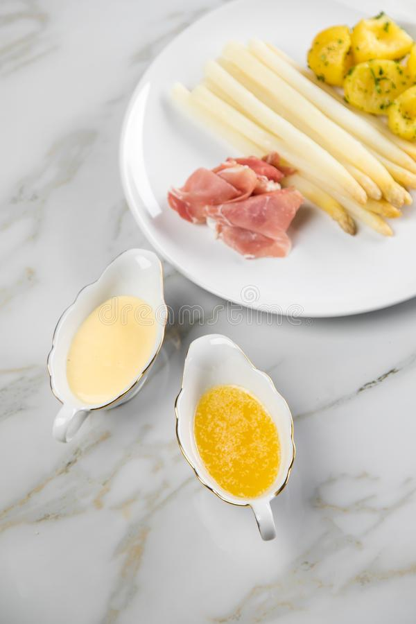 White German asparagus with potatoes, smoked ham, sauce boat with Hollandaise and melted butter on plate and marble background. White German speciality asparagus stock images