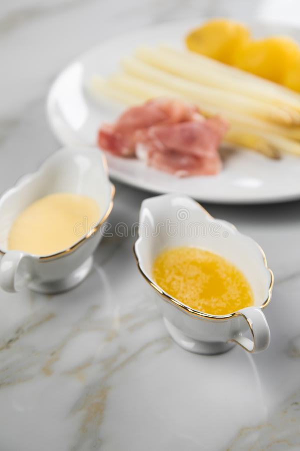 White German asparagus with potatoes, smoked ham, sauce boat with Hollandaise and melted butter on plate and marble background. White German speciality asparagus stock image