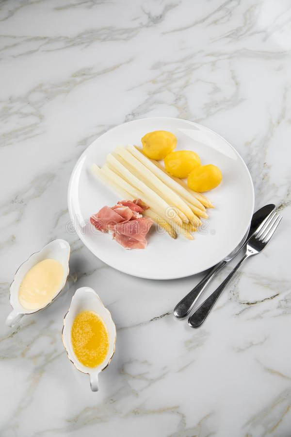 White German asparagus with potatoes, smoked ham, sauce boat with Hollandaise and melted butter on plate and marble background. White German speciality asparagus stock photos
