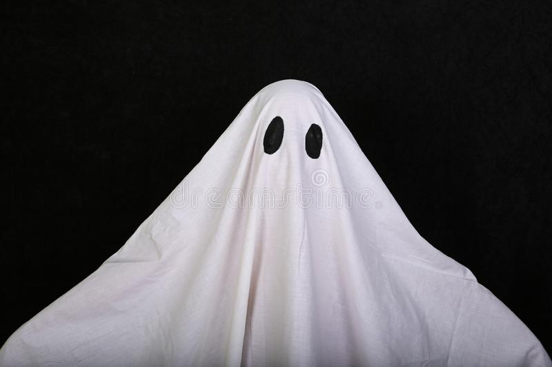White Ghost on black background. Halloween holiday party. royalty free stock image