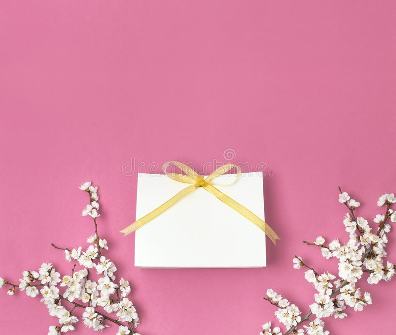 White gift bag with gold ribbon and branch of spring white flowers on bright pink background. Greeting card with delicate flowers stock photography