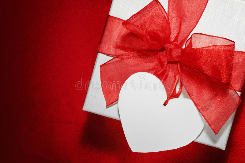 White gift box. With blank tag on red background royalty free stock image