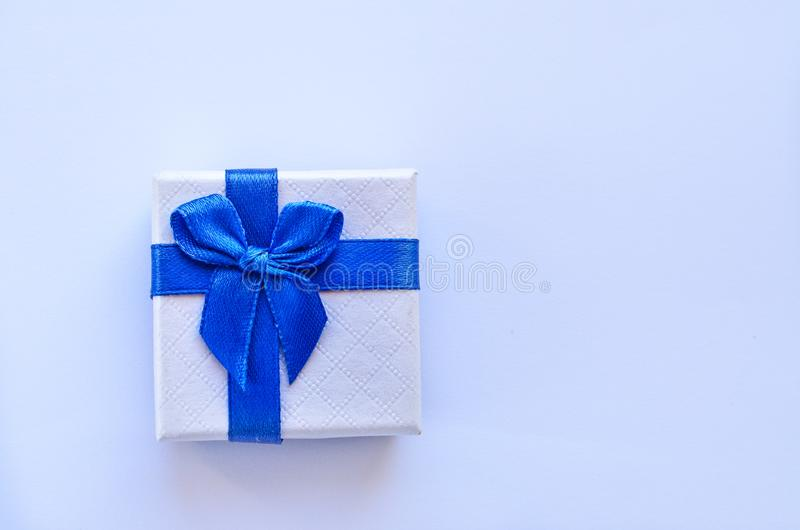 White gift box with a blue ribbon on a white background stock image