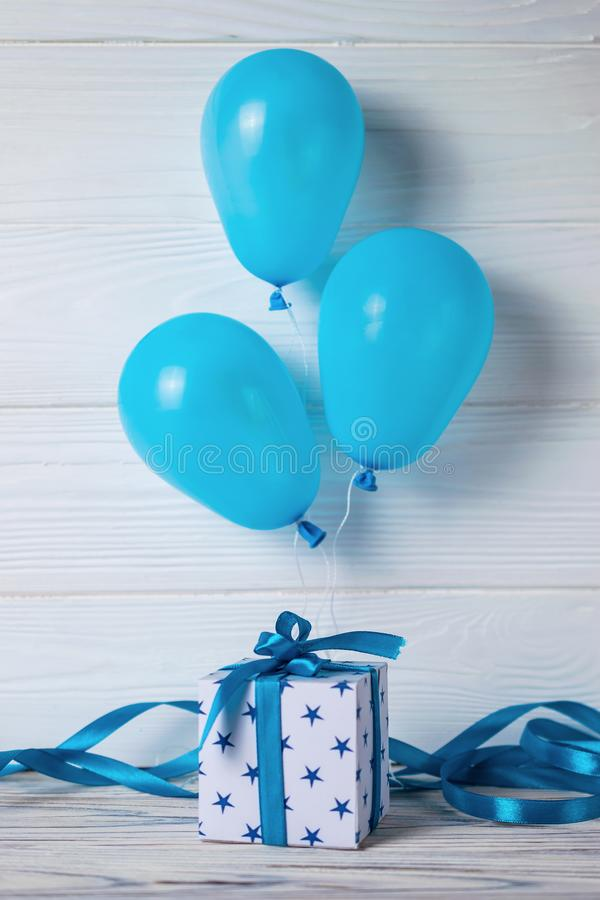 White gift box with blue ribbon and balloons. Happy birthday card royalty free stock images