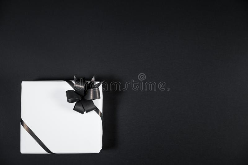 White gift box on a dark contrasted background, decorated with a. Textured bow, creating a romantic atmosphere. Typically used for birthday, anniversary royalty free stock photo