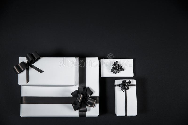 White gift box on a dark contrasted background, decorated with a textured bow, creating a romantic atmosphere. Typically used for birthday, anniversary royalty free stock image
