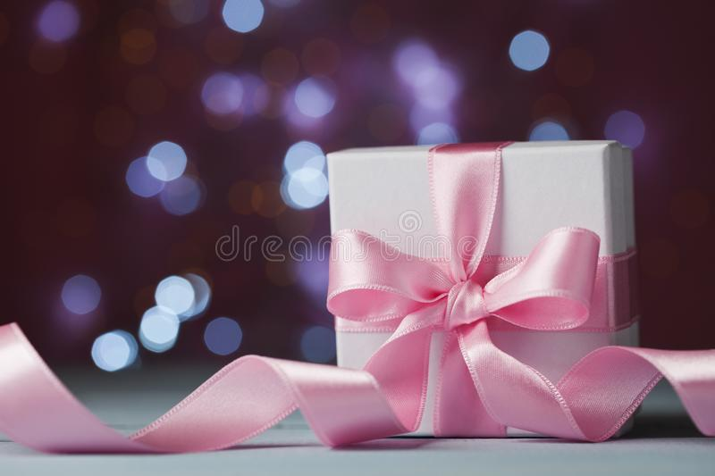 White gift box or present against magic bokeh background. Greeting card for Christmas, New Year or wedding. royalty free stock photos