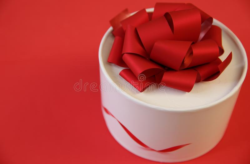 White gift box with red big bow isolated on a red background. Christmas, Valentine`s Day, Birthday other holidays. With copy space stock photography