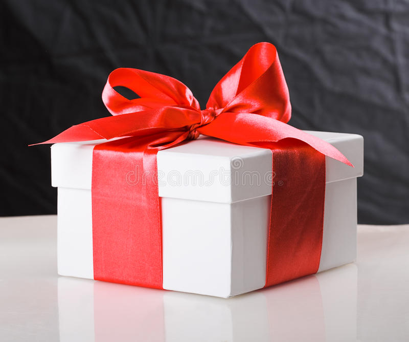 White gift box. With red ribbon bow on black background royalty free stock photo