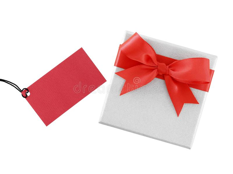 White gift box with simple red ribbon bow and blank crimson red greeting card for writing message isolated on white background. Presents and invitations for royalty free stock images