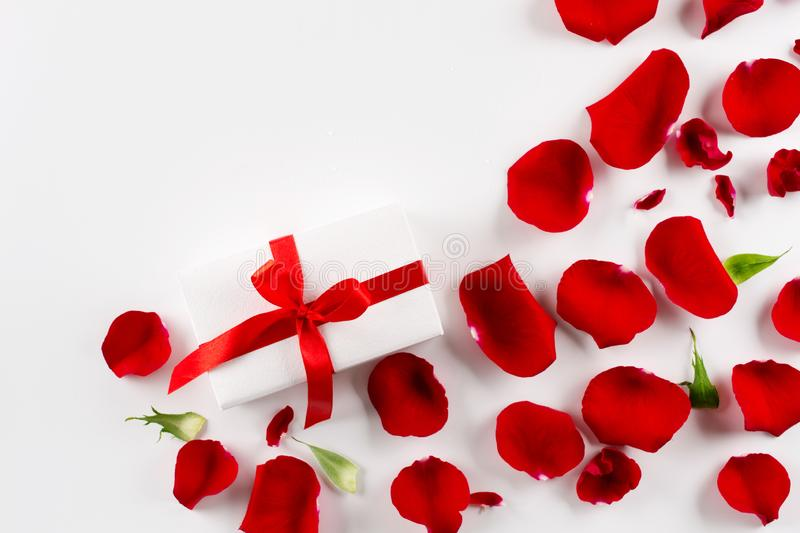 White gift box with red ribbon red velvet rose petals on white background. stock images