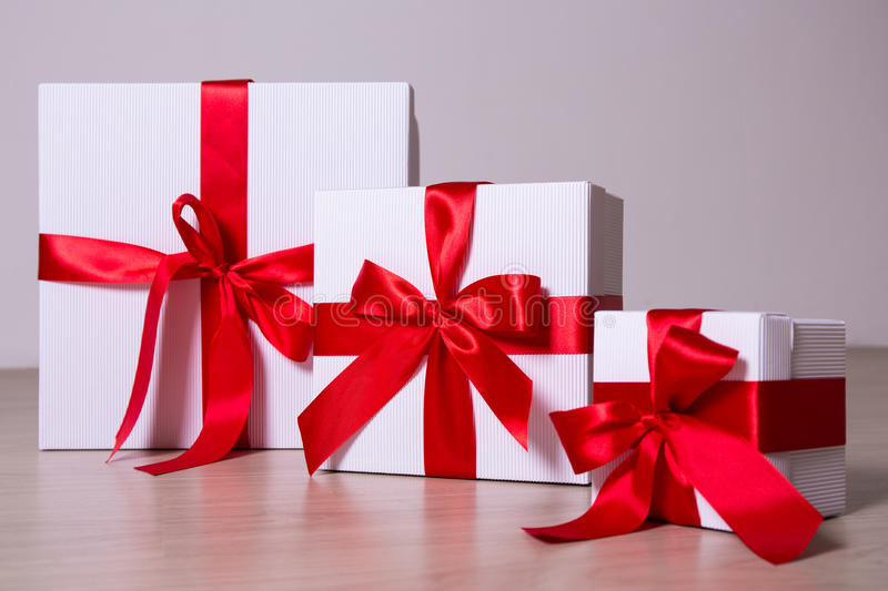 White gift boxes with red ribbon on wooden background royalty free stock photos
