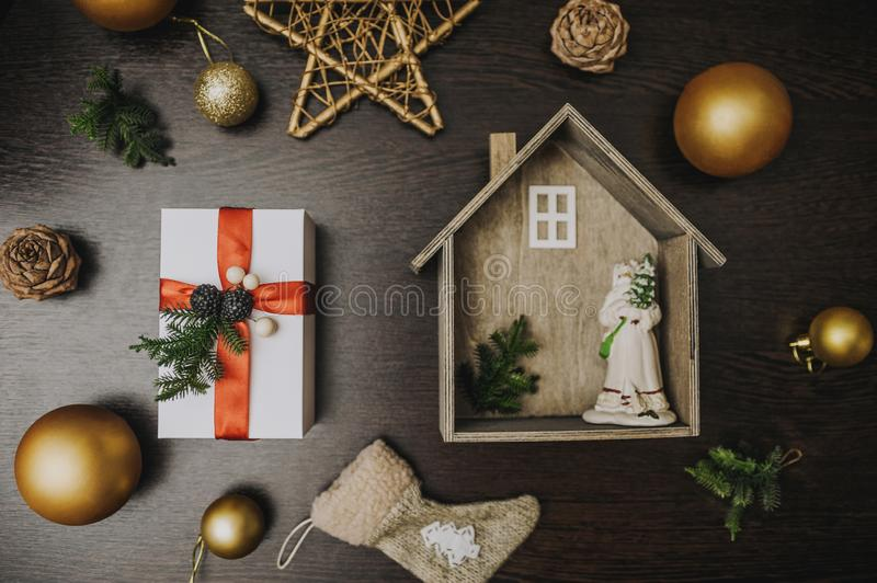 White gift and a house with Santa. against the background of a festive decor and blackboard. Lifestyle, christmas, new, year, holiday, surprise, happy, special stock images