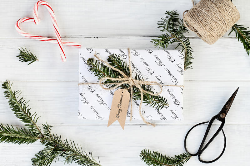 White Gift with Merry Christmas Tag. Beautiful gift with Merry Christmas tag. Decorated naturally with pine tree twigs and twine over a white background with royalty free stock photo