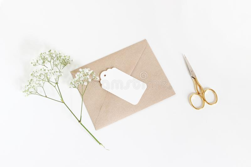 White gift tag with craft paper envelope, golden scissors and baby`s breath Gypsophila flowers isolated on white table. Background, wedding or birthday styled royalty free stock image
