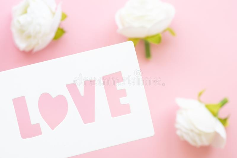 White gift tag with inscription love on a pink background. stock photo