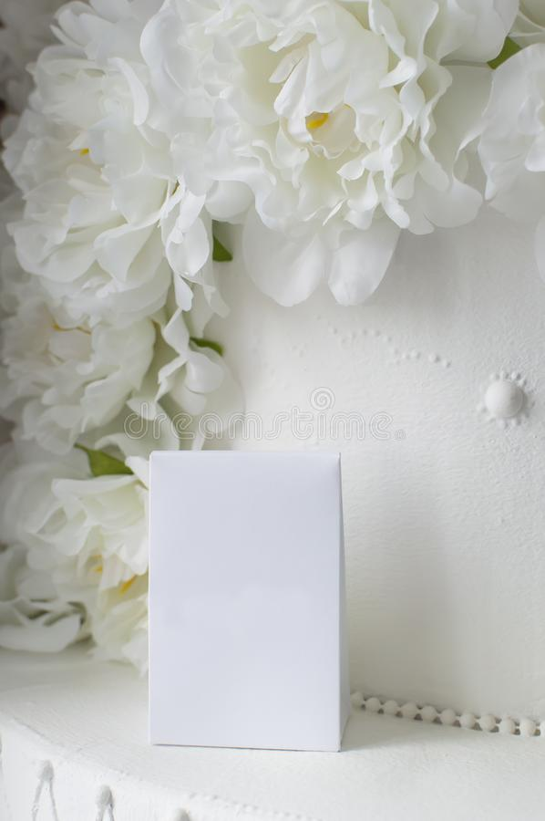 White gift wrap on a background of decorative artificial flowers. Close-up stock image
