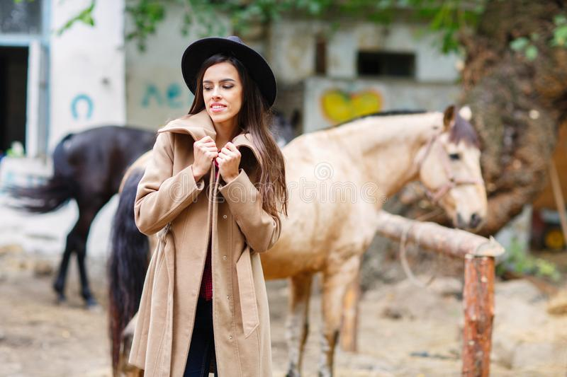 A white girl in a hat and coat is standing and smiling beside the horses. stock photography