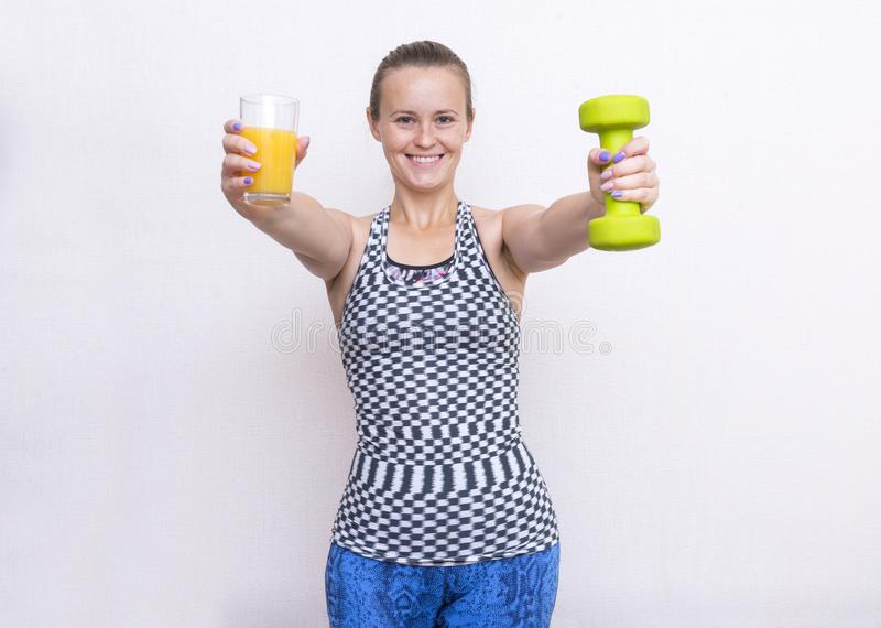 white girl holding a glass of juice and a dumbbell, a young woman smiling, a girl in sportswear stock photo