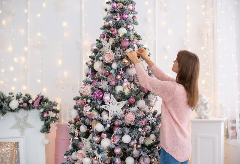 White girl in a knitted dress pink decorates a Christmas tree with Christmas toys royalty free stock photo