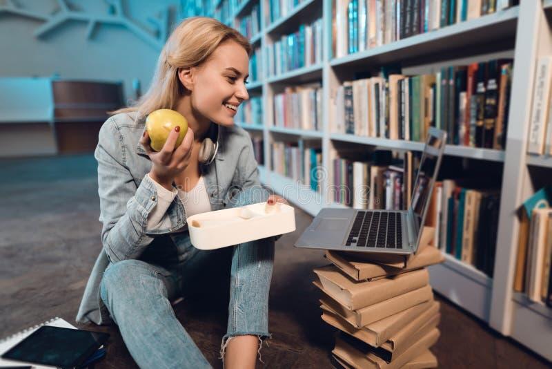 White girl near bookshelf in library. Student is eating apple from lunchbox. stock image