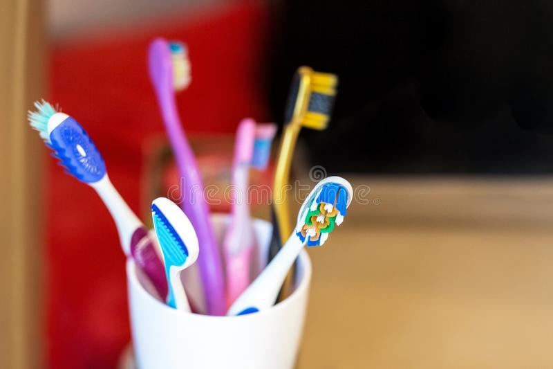 White glass with lots multicolored toothbrushes. Dental care and oral hygiene. Tongue cleaning. Big family concept royalty free stock photos