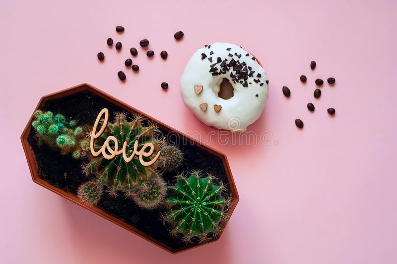 White glazed donut with black chocolate sweets with small cactuses. Food creative concept. Green Neon Mood on Pink background stock photo